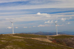 Wind energy turbines. In a landscpae over a beautiful blue sky royalty free stock photo