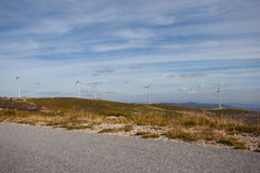 Wind energy turbines. In a landscpae over a beautiful blue sky royalty free stock images