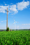 Wind energy turbines and old transmission tower on the field. Wind energy turbines and old transmission tower on the green field with blue sky royalty free stock photo