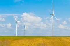 Wind energy turbines are one of the cleanest, renewable electric energy source, under blue sky with white clouds Stock Photo