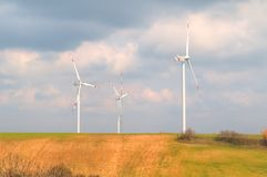 Wind energy turbines are one of the cleanest, renewable electric energy source, under blue sky with white clouds Stock Photos
