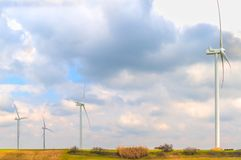 Wind energy turbines are one of the cleanest, renewable electric energy source, under blue sky with white clouds Royalty Free Stock Images