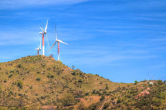 Wind energy turbines are one of the cleanest, renewable electric energy source, under blue sky with white clouds Stock Image