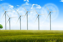 Wind energy turbines spinning on a field on a summer day Royalty Free Stock Photography