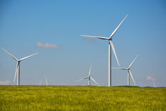 Wind energy turbines spinning on a field on a summer day Stock Photos