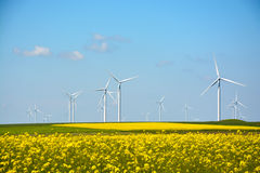 Wind energy turbines spinning on a field on a summer day Royalty Free Stock Images