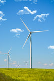 Wind energy turbines spinning on a field on a summer day Royalty Free Stock Photos