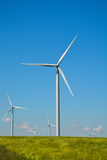 Wind energy turbines spinning on a field on a summer day Royalty Free Stock Photo