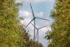 Wind energy turbines among trees Stock Photos