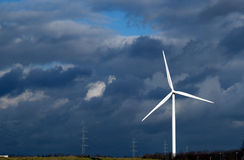 Wind energy. Windmill turbine generate wind green energy and dramatic clouds on the sky Stock Images