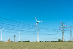 Wind engines and power supply lines on a sunny day Stock Photos