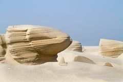 Wind erosion in the sand of a beach. Wind erosion forms strange sculptures in the sand of a beach royalty free stock photography