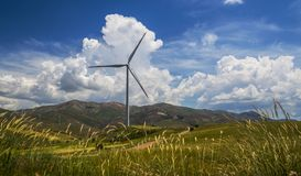 Wind power station among rural landscape Stock Photos