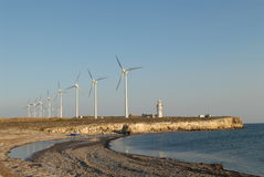 Wind farm, beacon and sea. Windturbines and beacon at aegean sea, Bozcaada - Turkey Royalty Free Stock Photography