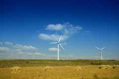 Wind farm at farmland against blue sky Stock Image