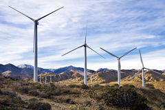 Wind Farm Five. Wind turbines cluster on a ridge against a cloud-streaked blue sky near Palm Springs, California Stock Images