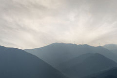 Wind farm on grey day, hills. Stock Photography