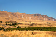 Wind Farm in the Hills. Modern wind turbines in the hills behind a farm and its barn Royalty Free Stock Images