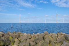 Wind farm in a lake along a dike below a blue sky. In spring royalty free stock photography