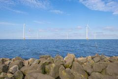 Wind farm in a lake along a dike below a blue sky. In spring stock photos