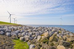 Wind farm in a lake along a dike below a blue sky. In spring royalty free stock photos