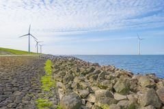 Wind farm in a lake along a dike below a blue sky. In spring stock photography