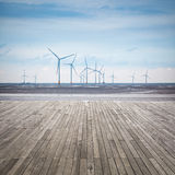 Wind farm in mud flat with wooden floor Royalty Free Stock Photo