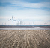 Wind farm in mud flat with wooden floor Royalty Free Stock Images