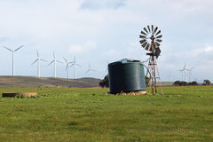 Wind Farm Old and New. An old windmill against the backdrop of a modern windfarm. This wind farm stretches for kilometres north west along the South Australian Royalty Free Stock Image