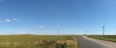 Wind farm panorama with blue sky. Panorama of  wind farm and access road on sunny summer's day Stock Images