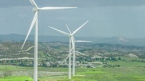 Wind farm in rural area. Wind turbines in green field rotating under stormy sky. Stock footage stock video footage