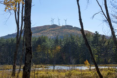 Wind farm seen from Quincy Bog, Plymouth, New Hampshire. Windmill farm on colorful ridge, with fall foliage of Quincy Bog below in Plymouth, New Hampshire Royalty Free Stock Images