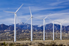 Wind Farm in Southern California. Wind turbines generate power near Palm Springs, California, against a backdrop of mountains and streaked sky Royalty Free Stock Image
