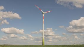 Wind farm stands in the green field, wind power generator on the background of the blue sky and floating clouds, sunny stock footage