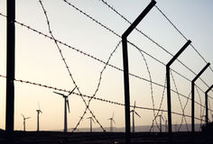 Wind farm after sunset. And barbed wire Royalty Free Stock Photo