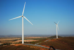 Wind farm turbines on Spanish farmland. Wind turbines or modern white windmills produce energy to power a city Royalty Free Stock Photos