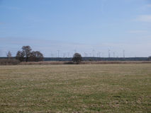 Wind farm with turbines viewed over a farm field. Wind farm with turbines viewed in the distance over a farm field in a concept of renewable, sustainable energy Royalty Free Stock Images