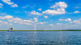 Wind Farm with Two and Three bladed Wind Turbines and a Fishing Boat on the Lake Stock Photography