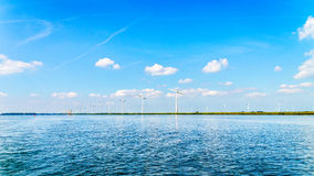 Wind Farm with Two and Three bladed Wind Turbines in a large Wind Farm along the Shore of Veluwemeer Royalty Free Stock Photos