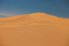 Wind-formed sand dunes. Against a blue sky stock image