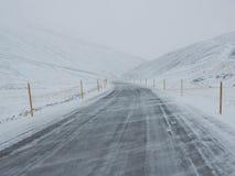 Wind geblazen sneeuw behandelde de winterweg met berg aan de kant van Royalty-vrije Stock Afbeelding