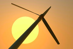 Wind generator. Windmill worth on a background of the orange sky Stock Photo