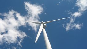 Wind generator on a background of blue sky and flying plane stock photography