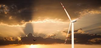Wind generator on a background of sunset sky Stock Images