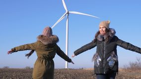 Wind generator, beautiful girlfriends are turning and pointing finger at windmill against sky stock footage