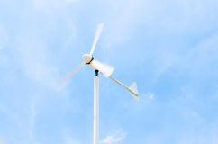 Wind generator on Cloudy sky. Cloudy Stormy sky with Wind generator working on the field Stock Photo