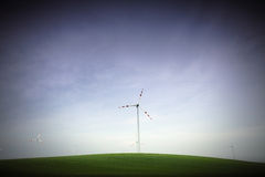 Wind generator on green hill. Wind electricity generator on a green hilly field with blue-purple skies Stock Images