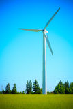 Wind generator in the meadows, on a background of blue sky. Stock Image