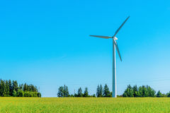 Wind generator in the meadows, on a background of blue sky. Royalty Free Stock Images