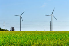 Wind generator in the meadows, on a background of blue sky. Royalty Free Stock Photos